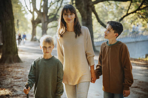 Mother and sons walking in public park on sunny day - MFF06429