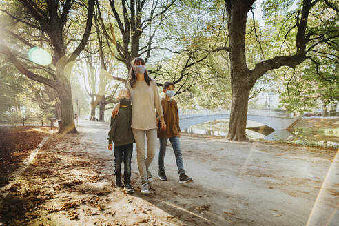 Mother and sons wearing protective face mask while walking in public park on sunny day - MFF06435