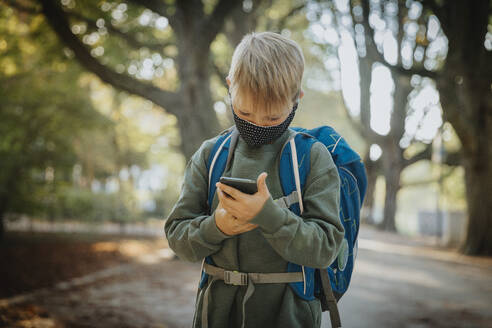 Boy text messaging on smart phone wearing protective face mask while standing in public park - MFF06438