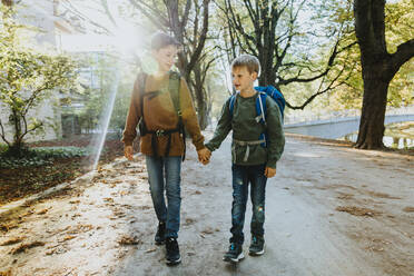 Boy holding hand of younger brother walking in public park on sunny day - MFF06441