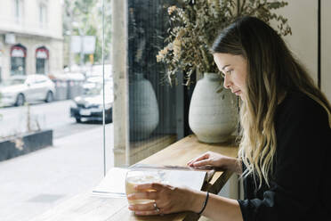 Businesswoman reading magazine while drinking coffee at coffee shop - XLGF00603