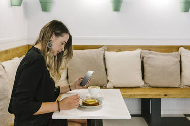 Businesswoman using mobile phone while eating cake at coffee shop - XLGF00606