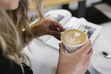 Woman holding cappuccino cup while sitting at coffee shop - XLGF00609