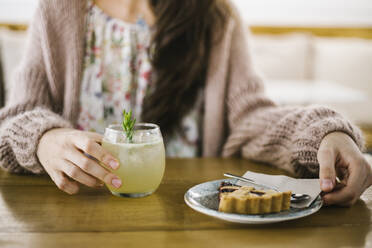 Mid adult woman having coffee and cake while sitting at coffee shop - XLGF00612