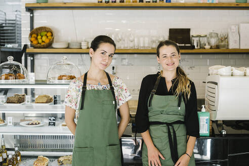 Smiling women standing by counter at coffee shop - XLGF00618