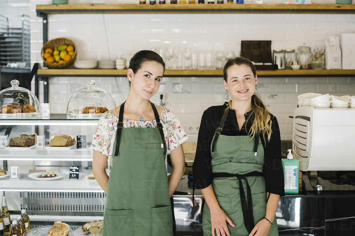Smiling women standing by counter at coffee shop - XLGF00618 - Xavier Lorenzo/Westend61