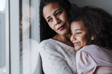 Mother and daughter looking through window while standing at home - EBBF00947