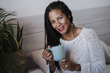 Smiling mature woman drinking coffee while sitting at home - EBBF00956