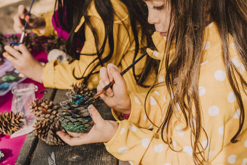 Cute girl coloring pine cone with sister at picnic table in park - ERRF04616