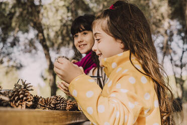 Smiling cute girl coloring pine cone with sister at picnic table in park - ERRF04622