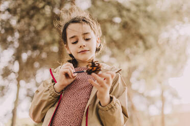 Cute girl coloring pine cone with paintbrush at park - ERRF04640