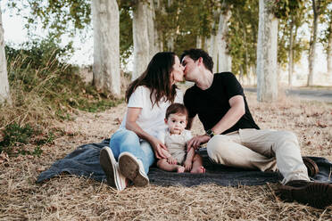 Parents kissing while sitting with baby bot on blanket outdoors - EBBF00992