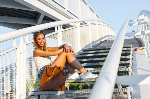 Smiling woman sitting on staircase at park - JMPF00481