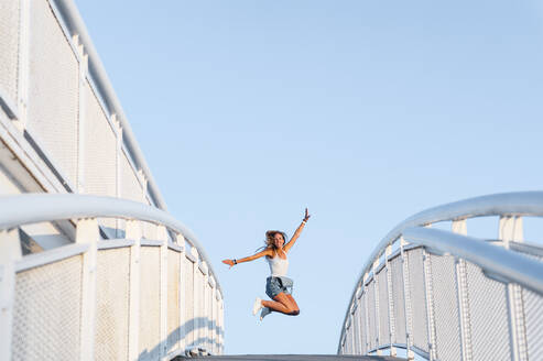 Mid adult woman with arms outstretched enjoying while jumping against clear sky - JMPF00487