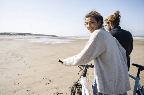 Smiling beautiful woman walking with bicycle by boyfriend while looking over shoulder at beach against clear sky on sunny day - UUF21766