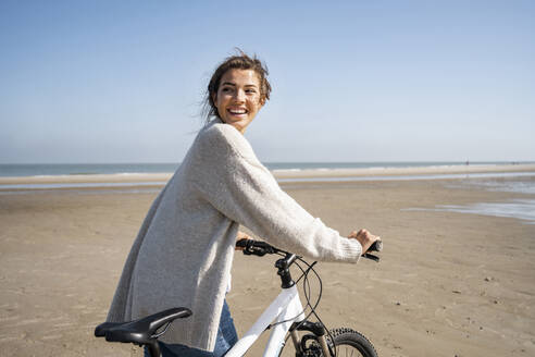 Cheerful young woman walking with bicycle while looking over shoulder at beach on sunny day - UUF21769