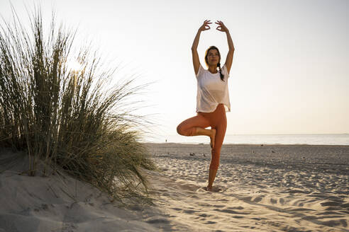 Beautiful young woman practicing tree pose with arms raised by plant on sand at beach against clear sky during sunset - UUF21775