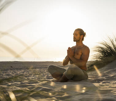 Shirtless young man meditating while practicing yoga sitting with hands clasped at beach against clear sky during sunset - UUF21787