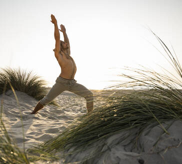 Shirtless young man practicing warrior position yoga at beach against clear sky during sunset - UUF21790