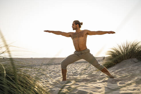 Shirtless man practicing warrior 2 position yoga at beach against clear sky during sunset - UUF21793