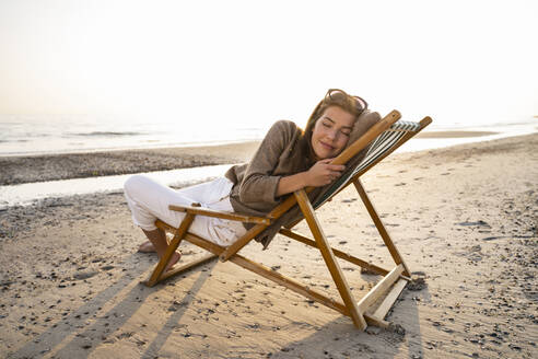 Relaxed woman reclining on folding chair at beach against clear sky during sunset - UUF21802