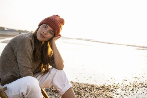 Beautiful young woman wearing knit hat sitting at beach during sunset - UUF21808