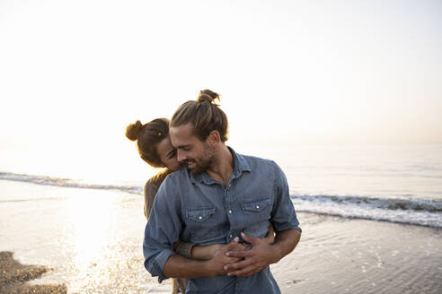 Woman embracing boyfriend from behind at beach against clear sky during sunset - UUF21823