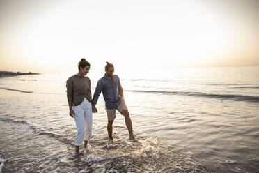 Happy young couple holding hands while walking on shore at beach during sunset - UUF21826