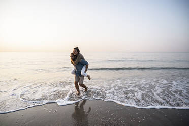 Cheerful man giving piggyback to girlfriend while walking on shore at beach against clear sky during sunset - UUF21829