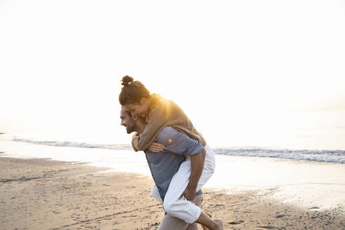 Smiling man giving piggyback to girlfriend while walking on shore at beach against clear sky during sunset - UUF21832