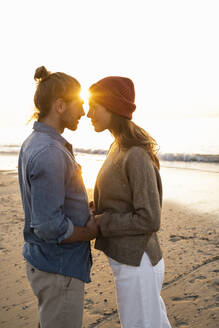 Romantic young couple standing face to face at beach during sunset - UUF21835