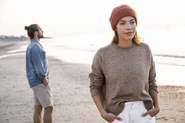 Beautiful young woman standing with hands in pockets against boyfriend at beach during sunset - UUF21847