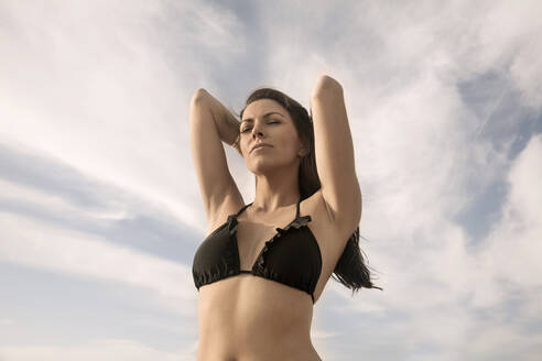 Beautiful woman standing with eyes closed and hand in hair against clear sky - AJOF00322