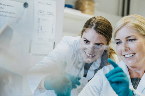 Smiling scientist and assistant discussing while examining human brain microscope slide at laboratory - MFF06459