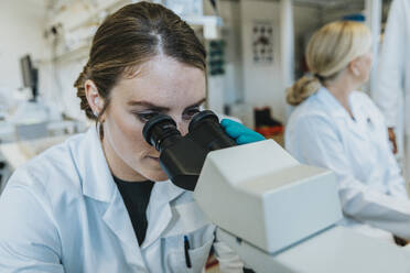 Assistant analyzing human brain microscope slide under microscope while sitting with scientist in background at laboratory - MFF06492