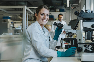 Smiling woman analyzing human brain slide under microscope while sitting with scientists in background at laboratory - MFF06495