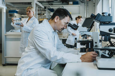 Male scientist sitting by microscope while coworker working in background at laboratory - MFF06501