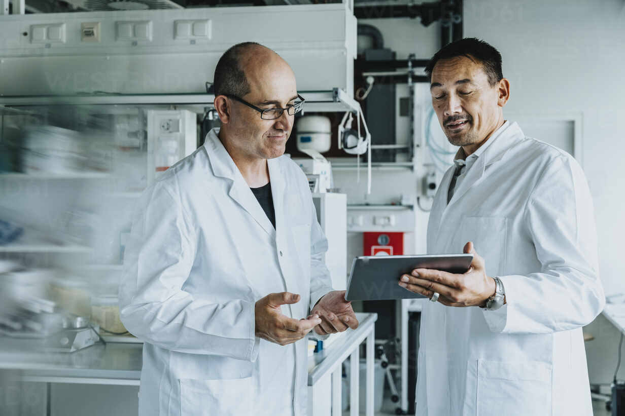 Scientist using digital tablet while standing at laboratory  - MFF06534 - Mareen Fischinger/Westend61
