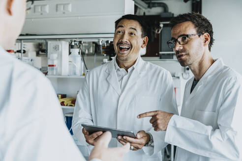 Scientist team using digital tablet while standing at laboratory - MFF06537
