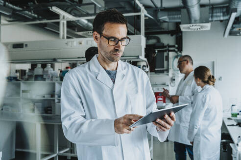 Scientist wearing eyeglasses using digital tablet while standing with coworker in background at laboratory - MFF06567