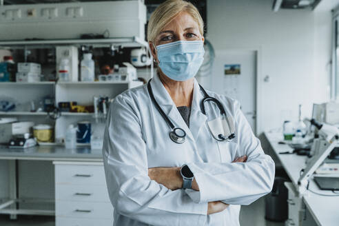 Confident scientist wearing face mask standing with arms crossed at laboratory - MFF06573