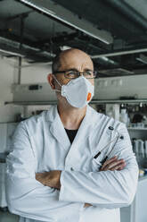 Scientist wearing face mask looking away while standing with arms crossed at laboratory - MFF06585