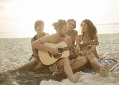 Man playing guitar while his friends enjoying sitting on sand at beach - AJOF00363