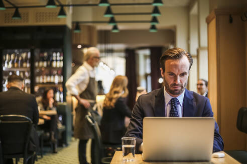 Businessman using laptop while sitting in restaurant - MASF20057