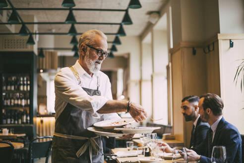 Waiter holding plates in restaurant - MASF20066