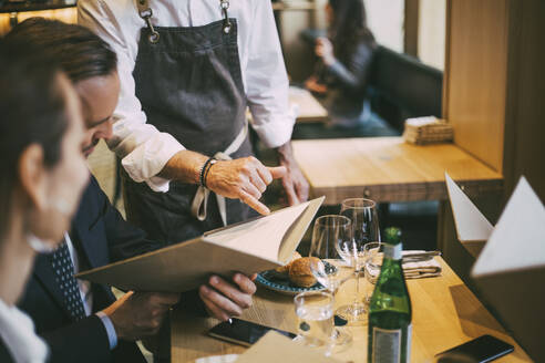 Midsection of waiter pointing at menu while business professionals sitting in restaurant - MASF20075