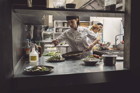 Female chef preparing food in commercial kitchen - MASF20150