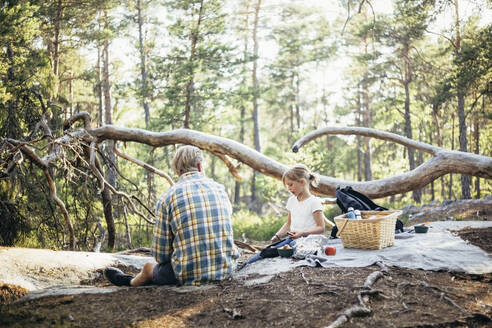 Daughter sitting with father on picnic blanket and using phone in forest - MASF20172