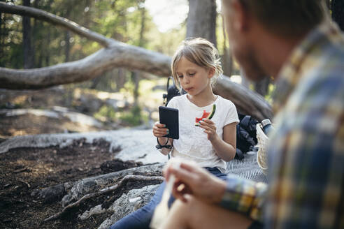 Daughter eating watermelon while using phone by father in forest - MASF20175