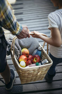 Father and daughter holding picnic basket full of apples on footbridge - MASF20199